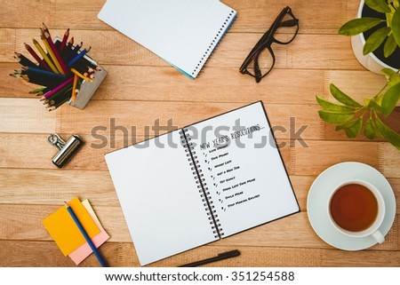 List of new years resolution on white background against close up view of business stuff - stock photo