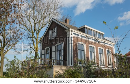Listed mansion built in 1889 as a doctor's residence and still used as such in a small village in the Netherlands. It's a sunny day in the fall season. - stock photo