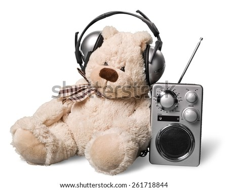 Listen. Retro toy Teddy Bear with headphones and radio receiver front mint green background - stock photo