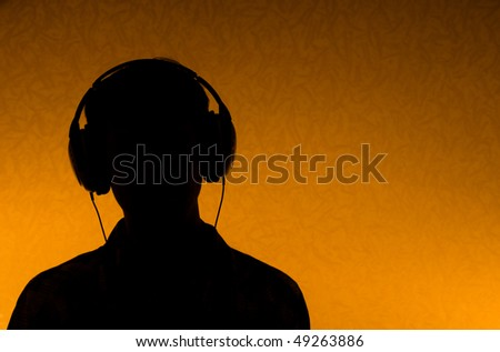 Listen to the Music - silhouette of man with earphones (back light) - stock photo