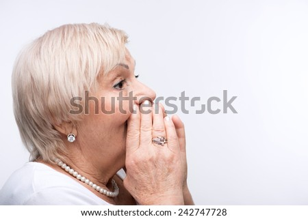 Listen up. Closeup portrait of elderly woman cupping her hands on mouth directing to copy space while standing against white background - stock photo