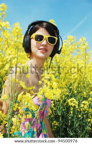 listening music on a field of spring canola flowers. - stock photo