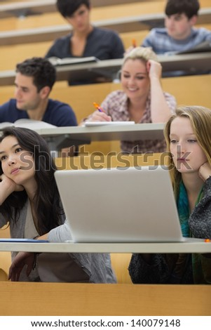 Listening students sitting in a lecture hall while taking notes and working with the laptop - stock photo