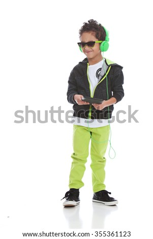Listening to Music.  Mixed race boy wearing headphones and holding a tablet.  Isolated on white.