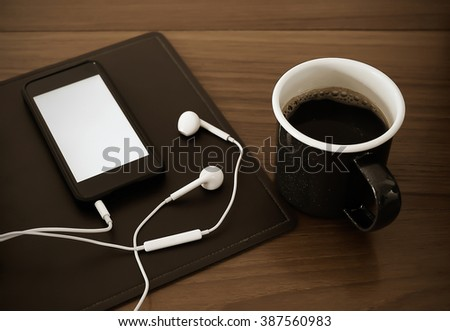 Listening to music on smartphone while drinking coffee, vintage style