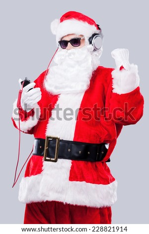 Listening to the Christmas music. Santa Claus in sunglasses and headphones listening to MP3 Player and gesturing while standing against grey background - stock photo