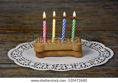 lit birthday candles in dog milk bones on lace paper doily and rustic wood
