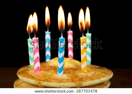 lit birthday candles on a stack of pancakes with butter and dripping syrup - stock photo