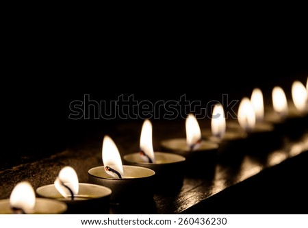 Lit candles in a row at night - stock photo