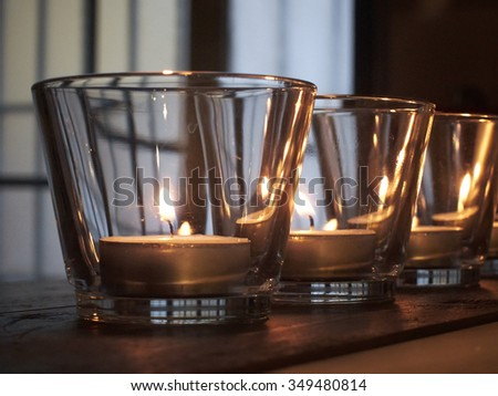lit candles in glasses on rustic wooden shelves - stock photo
