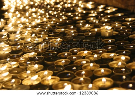 Lit candles in the dark of a church