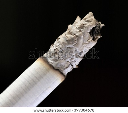 lit Cigarette with ash on black background - stock photo