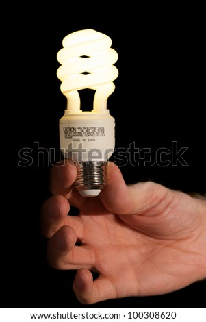 Lit Compact Fluorescent Light Bulb in Hand - stock photo