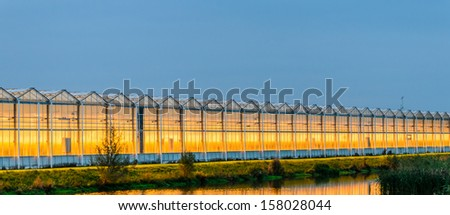 Lit greenhouse at night - stock photo