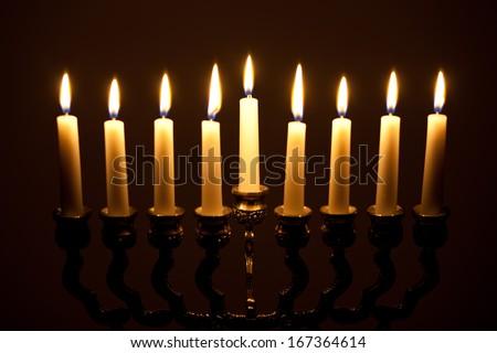lit hanukkah menorah on black - stock photo