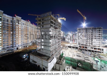 Lit high multi-storey buildings under construction and cranes at dark night. - stock photo