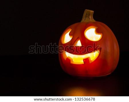 Lit jack-o'-lantern on black background. - stock photo
