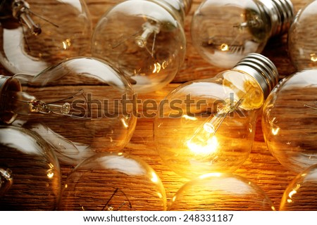 lit light bulb among unlit ones on wood