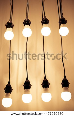 Lit lightbulbs hanging on wires against wall