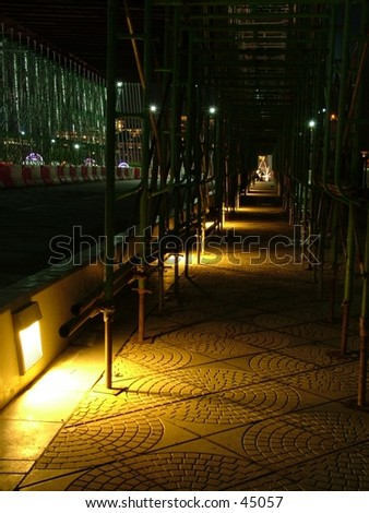 Lit pavement at night at a bridge under construction