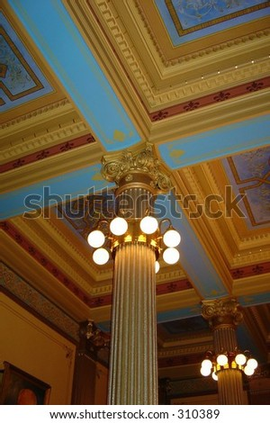 lit roman revival columns in elegant hall- painted crown molding on ceiling