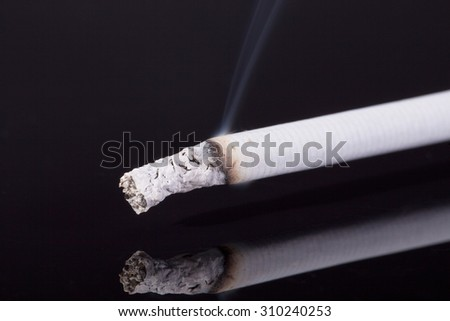 lit single cigarette with smoke isolated on black background -macro