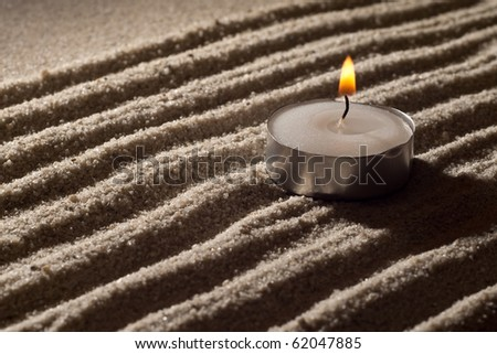 Lit Tea Candle on White Sand in Abstract Lighting