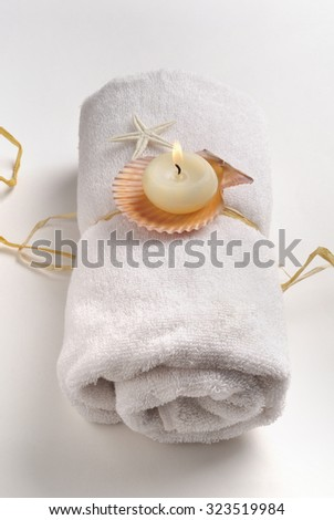 Lit-up scented candle with natural shells placed on rolled white towel - spa still life - stock photo