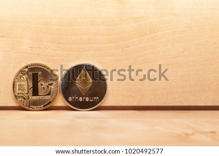 Litecoin (LTC) and Ethereum (ETH) coins in front of wood