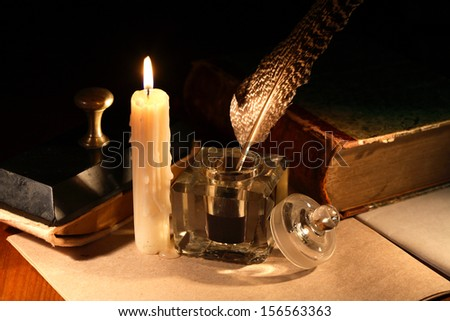 Literature concept. Stylish vintage inkwell near old book and candle on dark background
