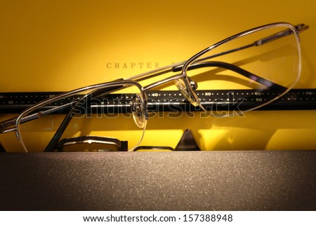 Literature inspiration. Closeup of eyeglasses on electrical typewriter with yellow paper sheet - stock photo
