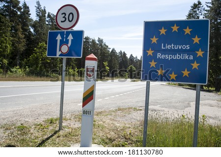 Lithuania country border sign between Latvia and Lithuania with coat of arms and flag. - stock photo