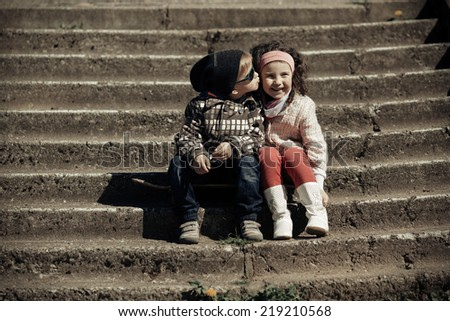 litle happy boy kissing girl on stairway - stock photo