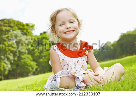 Litle loughing girl sitting on the grass in park