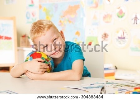 Litlel child in the classroom  gently  holding  a globe - stock photo