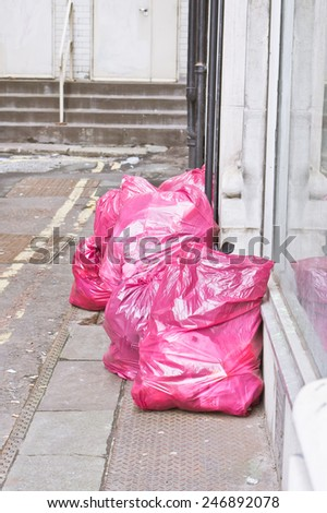 Litter in pink bags for collection, on a city street - stock photo