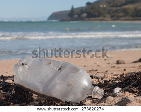 littered plastic bottle washed up on a beach in New Zealand  - stock photo