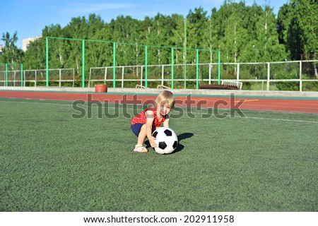 Little active football fan running on the green grass field with ball - stock photo