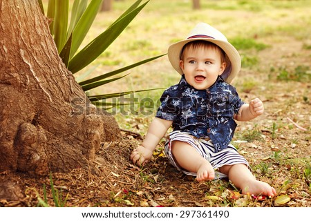 Little adorable baby boy in a straw hat and blue shirt sitting smiling near a tree on earth at sunset in summer - stock photo