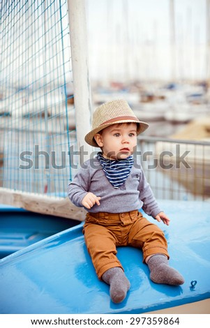 Little adorable baby boy in a straw hat and brown pants sitting on a blue boat on a background of yachts and the sea, summer - stock photo