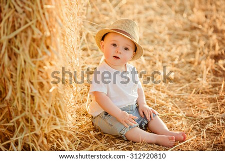 Little adorable baby boy with big brown eyes in a hat sits in a field near haystacks at sunset in the summer and looks serious eyes - stock photo