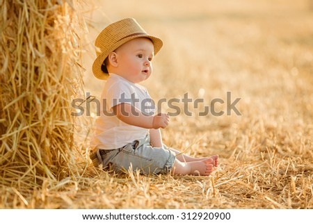 Little adorable baby boy with big brown eyes in a hat sits in a field near haystacks at sunset in the summer and looks into the distance - stock photo