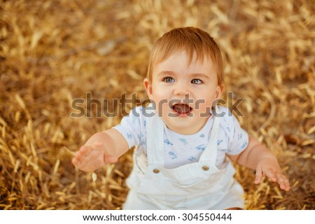 Little adorable chubby baby boy sitting in a white jumpsuit in the field in the spikelets in the warm rays of the setting sun in the summer, looks up - stock photo