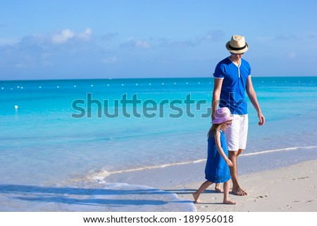 Little adorable girl and her father walking along the sea - stock photo