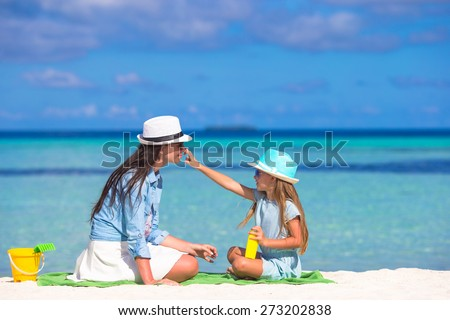Little adorable girl applying sun cream to her mother nose - stock photo