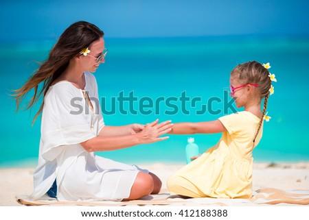 Little adorable girl applying sun cream to her mother nose - stock photo