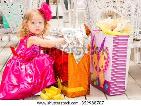 Little adorable girl celebrating 3 years birthday.  Kid  wearing flower hairband on party outdoors on summer day. Childhood.