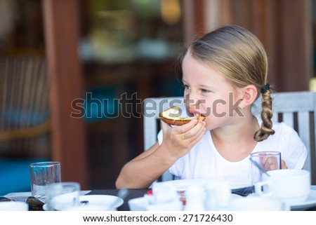 Little adorable girl eating bread with butter and honey on breakfast - stock photo