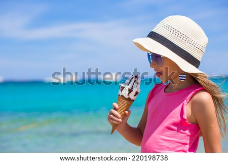 Little adorable girl eating ice cream on tropical beach - stock photo