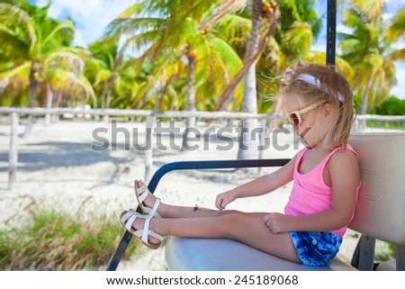 Little adorable girl in golf car at palm grove during tropical vacation - stock photo